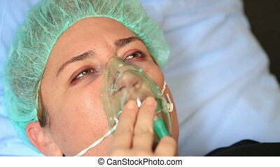 Patient with oxygen mask - Diseased woman wearing a oxygen...