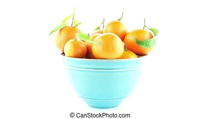Tangerines on ceramic blue bowl isolated on white background...