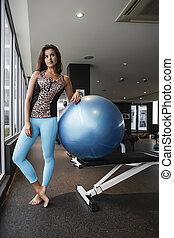 Girl leaning on a bouncy gym ball - Brunette girl in blue...