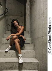 Woman in a black dress sitting on stairs