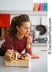 Woman with her eyes closed smelling a fresh mushroom