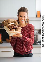 Smiling woman in kitchen holding up basket of fresh...