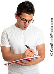Student in glasses writes in book - A male college or...
