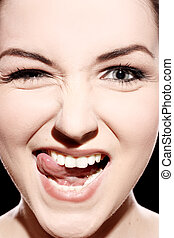 Funny face - A close up of a young woman pulling a...