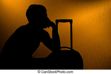 Traveling - silhouette of man and suitcase in the darkness