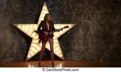 woman with electric guitar. sexy girl in leather, shining star in the background, slow motion