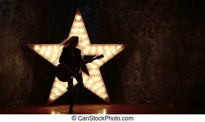 blonde girl with electric guitar in leather, shining star in...