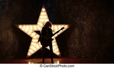 woman wearing leather jacket and playing a guitar, shining...