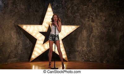 glamorous girl holding a mike and singing. shining star in the background, slow motion