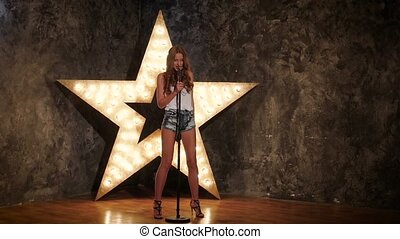 girl holding a mike and singing shining star in the...