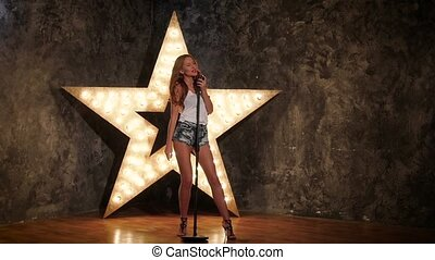 star girl holding a mike and singing, slow motion - Portrait...