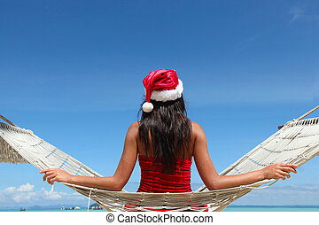 Christmas vacation - woman in santa hat on the beach in...
