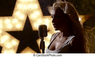 Beautiful female rocksinger with retro microphone, closed...