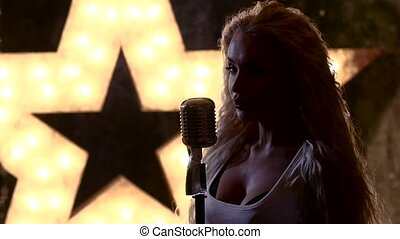 Beautiful blond female rocksinger with retro microphone,...