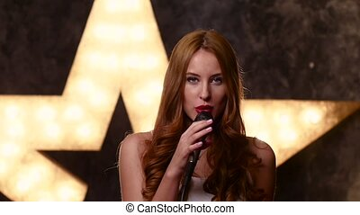 Stylish girl singing with a microphone, slow motion, close up
