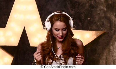 smiling teen girl with headphones in music studio, slow...