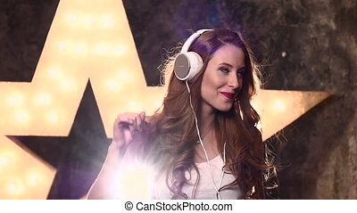 attractive smiling teen girl with headphones in music...