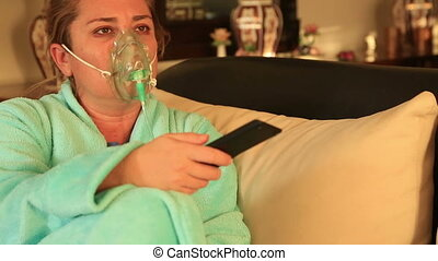 Woman with oxygen mask watching tv - Portrait of a diseased,...