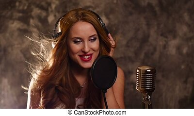 elegant girl listening to music and singing with Microphone,...