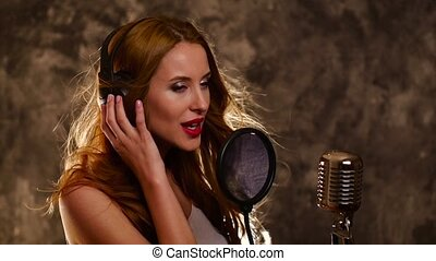 sexy girl listening to music on headphones and singing, slow...