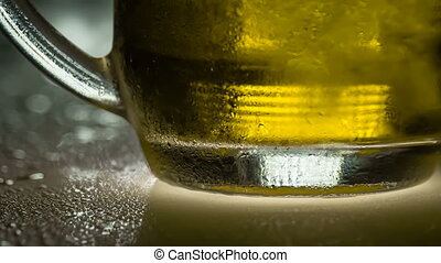 Steamy Cup of Cold Beer - A mug of beer on a wet surface is...