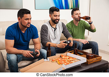 Male friends playing videogames - Group of three male...