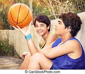Happy basketball players - Cute basketball players sitting...