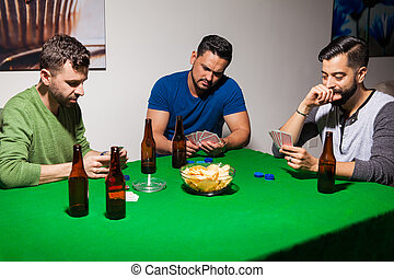 Three friends during poker night - Group of three male...