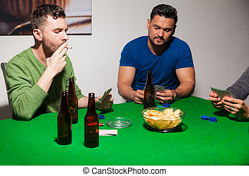 Men smoking during poker night - Group of male friends...