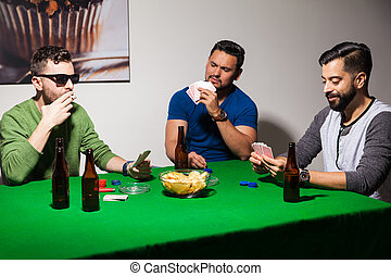 Friends playing poker at home - Group of friends playing...
