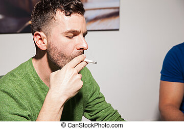 Young man smoking a cigarette - Portrait of a young Latin...