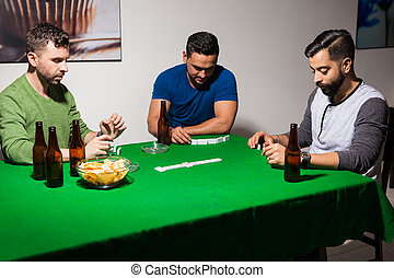 Young man playing dominoes at home - Group of three friends...
