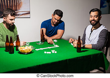 Drinking beer and playing dominoes - Three Hispanic friends...