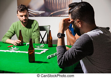 Men concentrated on a dominoes game - Male friends drinking...