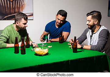 Male friends playing dice at night - Group of three Latin...