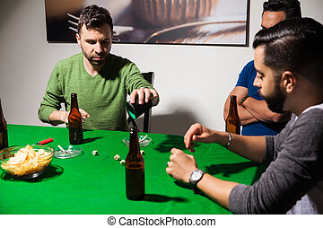 Guys playing dice on poker night - Portrait of a group of...
