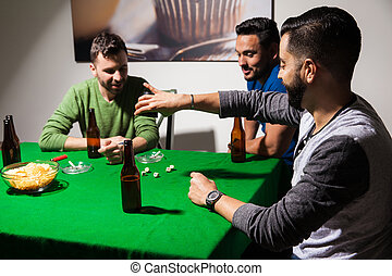 Men playing dice and drinking beer - Group of three guys...