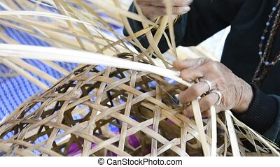 Weaving bamboo basket - elderly female hands manually...