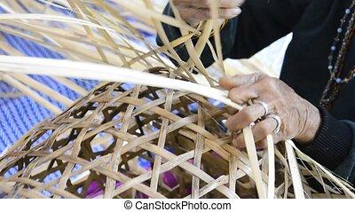 Weaving bamboo basket. - elderly female hands manually...