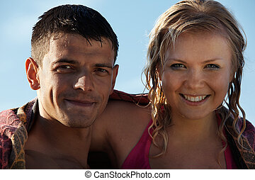 summer couple - young couple with wet hair posing in beach...