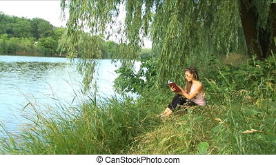 Girl reads the book on the bank of river