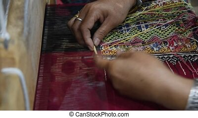 Traditional Cotton Woven - Hands of woman weaving sarong...