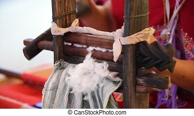 Spinning cotton fibers - Woman spinning wooden wheel prepare...