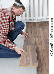 Laminate flooring installation - Man making the laminate...