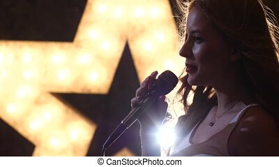 silhouette woman singer with microphone, shining star in the...