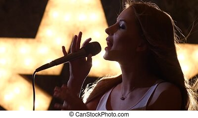 silhouette sexy woman singer with microphone, shining star...