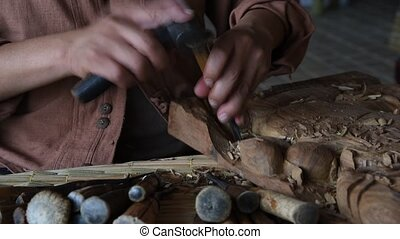 Wooden carving - Hands of the craftsman wooden carving a...