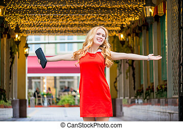 beautiful girl with outstretched hands in a red dress in the...