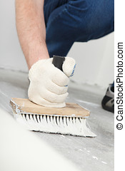flooring installation - man puts glue for a linoleum...
