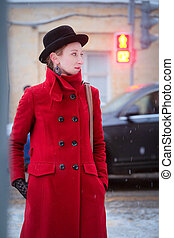 Girl in a red coat in a city